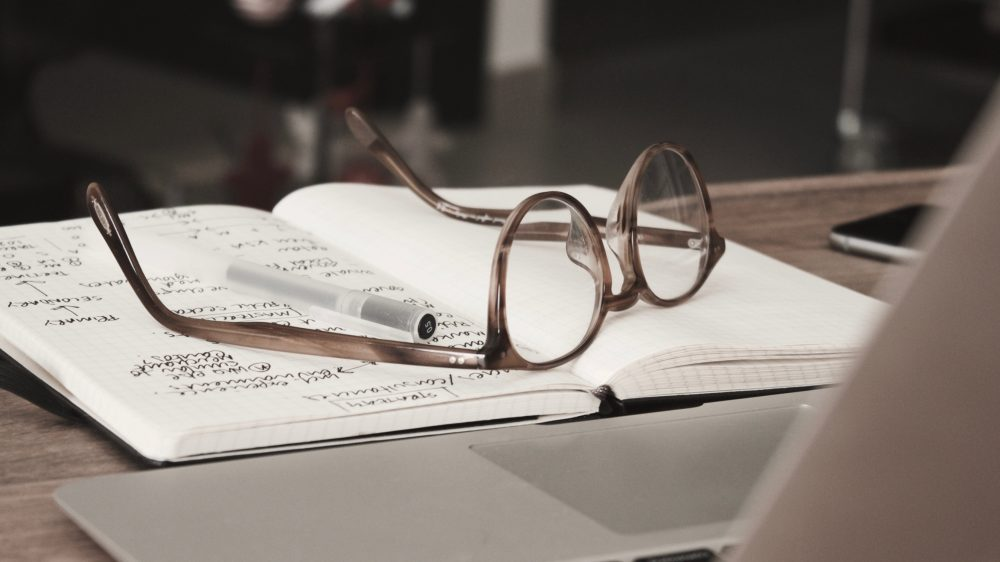 Present Tense in Spanish — a pair of glasses on an open notebook