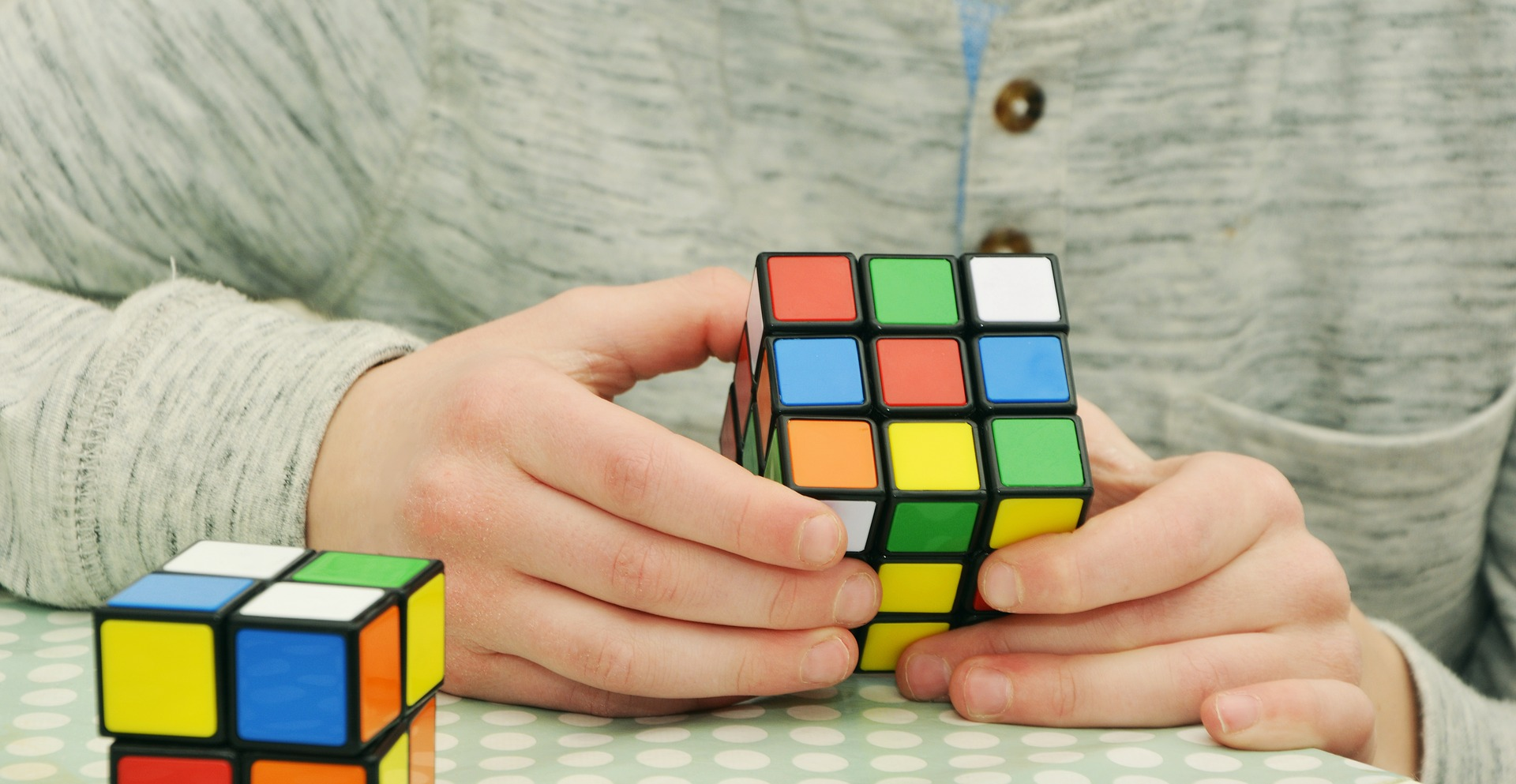 """Haber"" conjugation in Spanish — a person playing with a Rubik's cube"