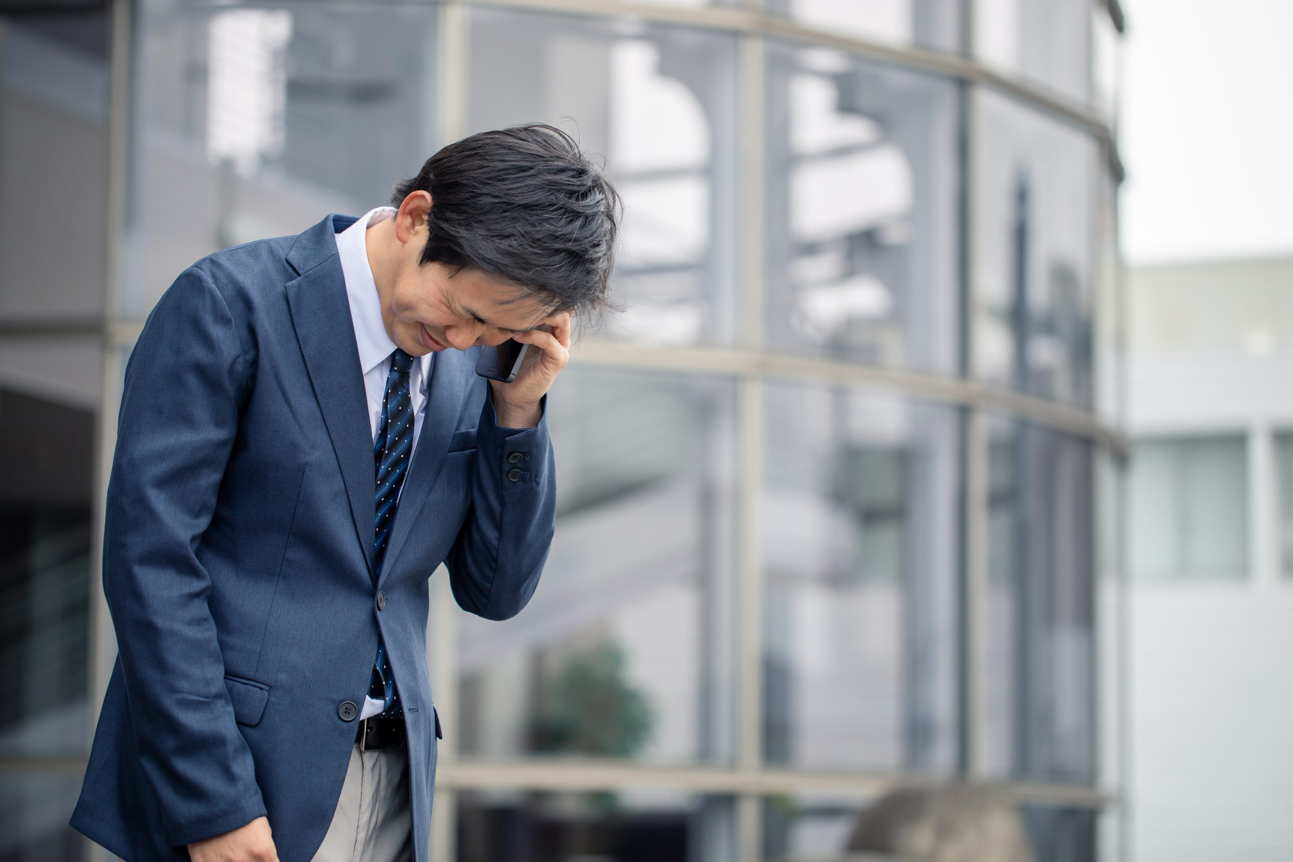 Japanese man in a suit apologizing over a phone