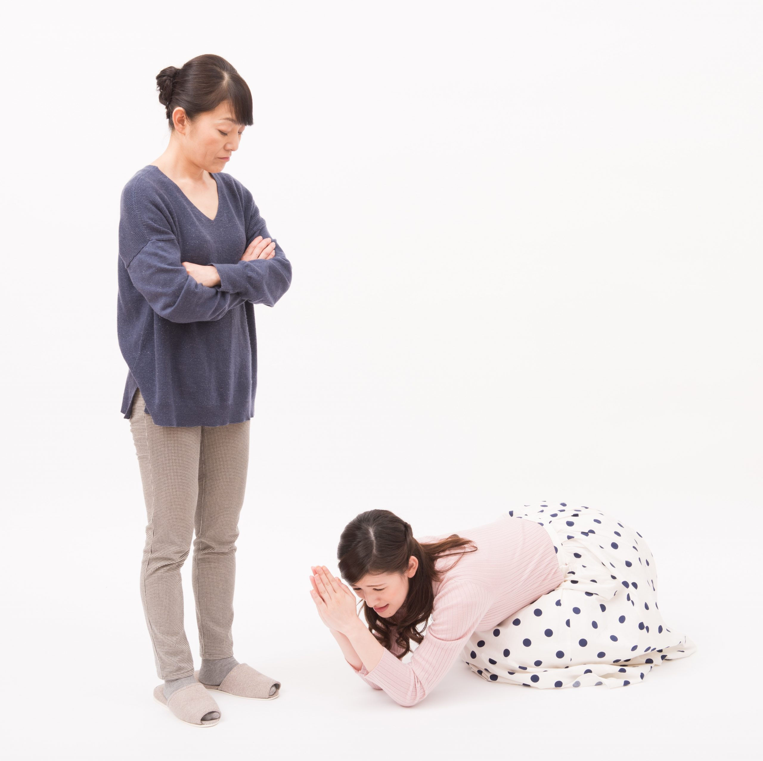 Japanese woman kneeling and apologizing to another woman