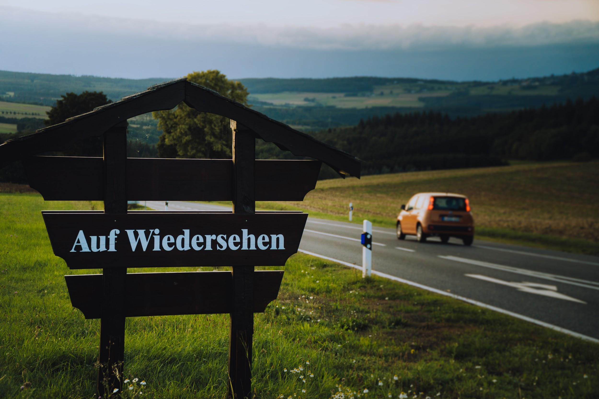 """""""Auf wiedersehen"""" (""""Goodbye"""" in German) on a roadside sign"""