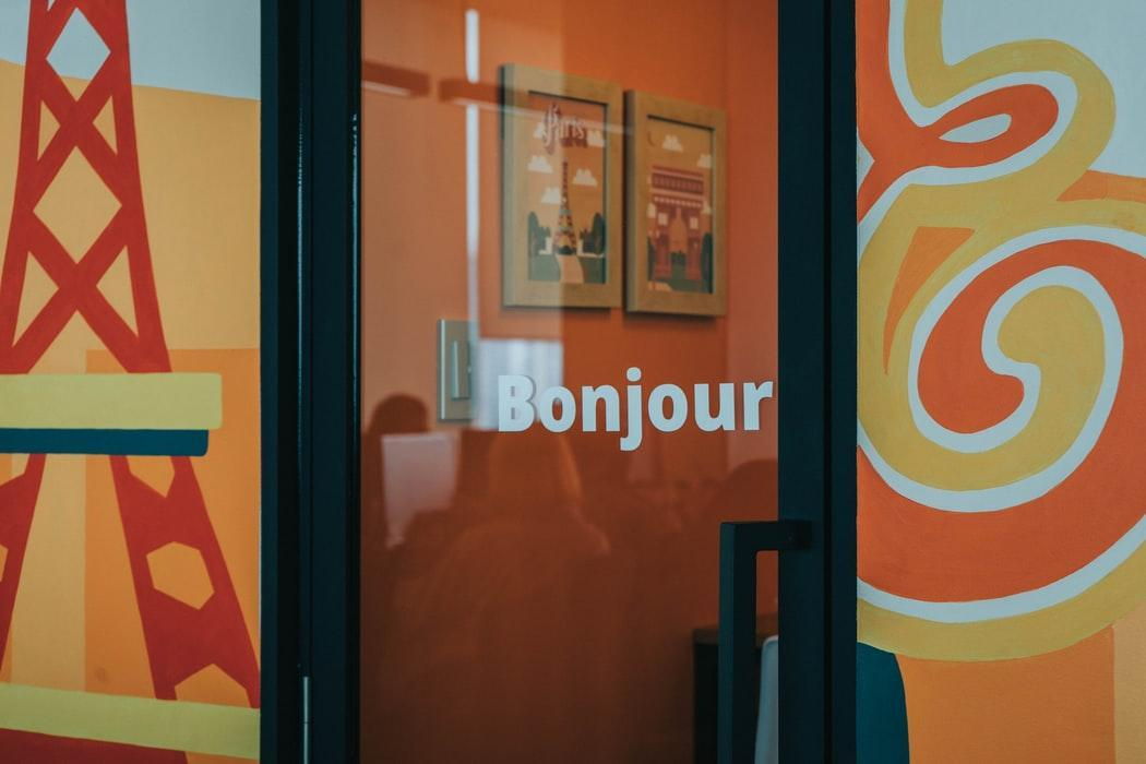 """""""Bonjour"""" (""""hello"""" in French) written on a glass door"""